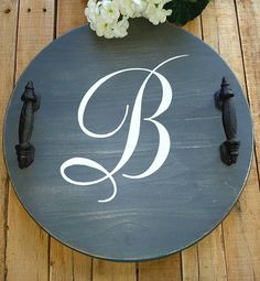 Dress up your décor with a beautiful personalized wood tray. Each tray is custom made to order. It is 18 in diameter and painted in white and elephant gray chalk paint. Then it is distressed to give it a slightly rustic or vintage look. To complete the tray, heavy wrought iron Gray Chalk Paint, White Chalk, Rustic Decor, Farmhouse Decor, Monogram Painting, Coffee Table Tray, Wood Tray, Decorating Coffee Tables, Diy Projects