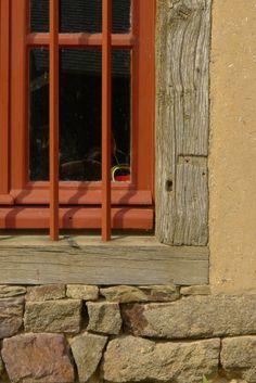 détail d'une double carrée de chêne sur un soubassement en pierre d'un mur en bauge enduit
