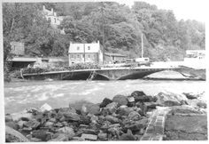 """The aftermath of Tropical Storm Agnes, looking north from Baltimore County toward the ruined bridge leading to Ellicott City. In the center, on the Howard County side, is 8000 Main Street, at that time utilized by Appalachian Outfitters. The site was later restored and used by the """"Old Emporium"""" in 1994. Also seen, on the hillside, is the Angelo Cottage.    Date: June 1972"""