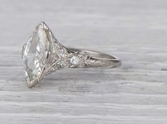 Antique Edwardian engagement ring made in platinum and centered with an approximately 1.20 carat EGL certified marquise cut diamond with G-H color and VS2 clarity. Circa 1915 Lovely Edwardian features