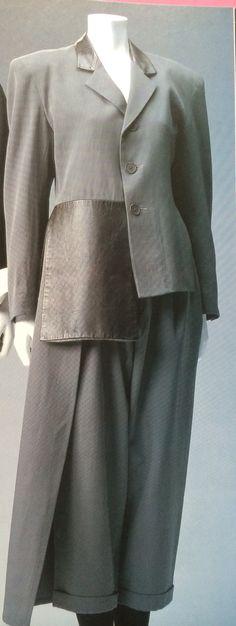 Yohji Yamamoto Pantsuit. Label: Yohji Yamamoto Autumn/Winter 1986. Gray-beige wool gabardine jacket and pants; brown leather patch on jacket; similar panel on pants.