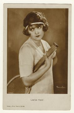 This vintage real photo postcard features European film star Liane Haid (1895-2000). She poses holding a tennis racket and wearing a hair band to keep her hair out of her eyes. She is quite beautif…