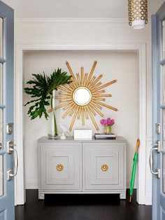 Sunburst Mirror: White walls and gold accent. Love the little splashes of green.
