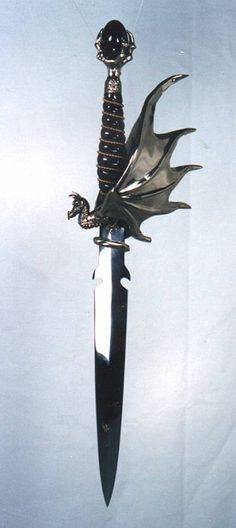 Draco Dagger, by Omega Artworks. One of our most ornate daggers. This is a large hilt. A detailed dragon at the base of the hilt with the wings of the dragon forming a knuckle guard. The pommel is a dragons claw with a egg shaped gemstone in it's grasp.