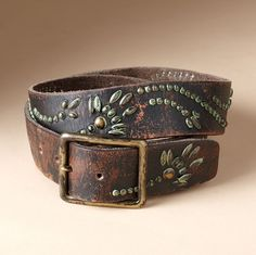 "VINTAGE VERDIGRIS BELT -- A fluid floral motif, picked out in studs weathered to look like verdigris-shaded brass, lends color and character to this distressed leather belt. Imported. Sizes S (32""), M (34""), L (36""). 1-1/2""W."