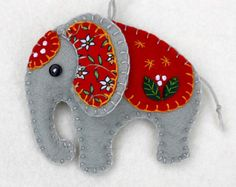 A handmade elephant ornament, in grey felt with hand-embroidered cap and saddlecloth in a range of bright colours. An unusual felt Christmas ornament, or a perfect gift for anyone who loves elephants. Please choose red, orange, green, teal, blue or purple from the drop-down menu. The listing is for one elephant, which measures approx. 3 x 3 inches ( 8 x 8 cm.)