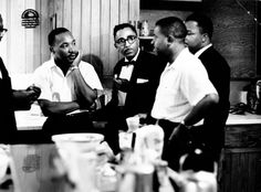 Martin Luther King Jr. (center) speaks with Rev. Ralph Abernathy (2nd from right) and others, 1961.