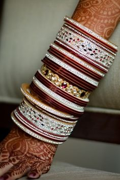 Bride's arm covered with henna and bangles for Indian wedding for the first year to indicate she is a new bride