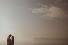 Couple stood on cliff top, overlooking Scarborough Castle and the seaside, at Cleveland Way, North Bay, Scarborough in Yorkshire.