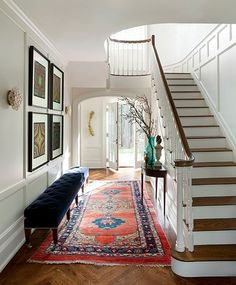 """Designer Frank Roop used an oversize tufted bench to add an """"unexpected or dramatic"""" element to the entryway of this Boston-area colonial home. Oh how I will love the day I have a house with a staircase like this one. Design Entrée, Deco Design, House Design, Design Ideas, Lobby Design, Hall Design, Design Trends, Modern Design, Interior Design Minimalist"""