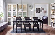 Ein großes Esszimmer u. a. mit INGATORP Ausziehtisch in Schwarz, INGOLF Stühlen in Schwarzbraun und LIATORP Vitrinenschränken in Weiß