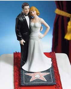"""Roll out the red carpet! This cake topper features you and your spouse as the newest Hollywood celebrity couple! This beautiful pair stand on a life-like Hollywood Walk of Fame star engraved with """"Mr. and Mrs."""" You will truly be the A-list stars of..."""
