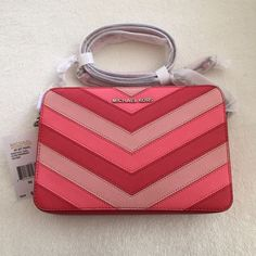 """MICHAEL KORS JET SET Chevron Large East West Cross NWT MICHAEL KORS JET SET Chevron Large East West Crossbody.  Color - Coral Chevron. Size - 9""""W ? 4""""H ? 3/4""""D. Adjustable crossbody strap with 23"""" to 25"""" drop.  Top zip closure.  Exterior includes silver - tone  hardware.  Interior Includes 3 open pockets. Saffiano leather; lining: polyester.  100 % Authentic! GUARANTEED. Michael Kors Bags Crossbody Bags"""