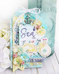 """Can you hear the sounds of the ocean waves? With the new St. Tropez line you'll have the beach and ocean right at your fingertips. I just love playing with this gorgeous, new collection while creating two beachy tags! The colors, designs, and accessories are perfect for any sea-faring adventure. I especially love the chipboard shapes with the adorable bicycle, toting a basket of flowers...and the retro beach umbrella and photo frame- highlighting a photo from one of my favorite tropical…"