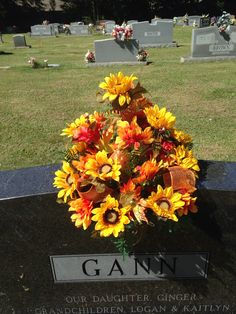 Cemetery vase using yellow sunflowers, orange mums and leaves as filler with shiny orange ribbon