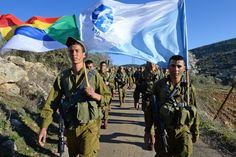 Soldiers of the Herev Battalion in a beret march holding up the battalion's flag and the official Druze flag.