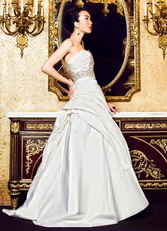 Strapless A line gown with a delicately ruched bodice that trancends into a dramatically draped skirt.  Accented with a stunning, heavily encrusted Swarovski crystal and moonstone belt that highlights the natural waist.