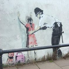 Police fouillant une petite fille Banksy