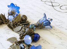 This stunning, eclectic Lucite flower charm bracelet features gorgeous colors of cobalt blue, capri blue, a hint of sky blue opal and violet. Several of these Lucite flowers are delicately airbrushed in two tones and wrapped in antique brass. This leaf charm bracelet also features our very own hand enameled Lucite flowers. These enameled flowers are layered with enamel on both sides