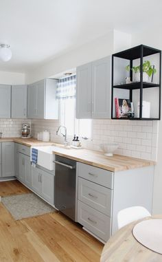 small kitchen remodel reveal on a budget with grey cabinets, oak wood flooring, stainless steel appliances, a farmhouse sink and more. Grey Kitchen Cabinets, Diy Kitchen, Kitchen Ideas, Soapstone Kitchen, Kitchen Countertops, Kitchen Sinks, Laminate Countertops, Kitchen Small, Design Kitchen