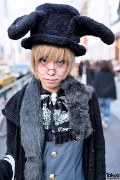 Dec 2013: Uri's outfit features a long Black Peace Now jacket over an Alice and the Pirates top, Alice and the Pirates breeches, striped socks, and Vivienne Westwood rocking horse shoes. Accessories include a rabbit ears hat, round glasses, a cameo, a fuzzy faux stole (with eyes), several Vivienne Westwood silver rings, and a Baby The Stars Shine Bright clock bag.