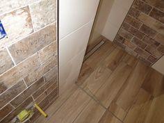 CIR Brick im Badezimmer mit Holzoptikfliesen auf dem Bodenbelag und der bodenebenen Dusche mit Duschrinne