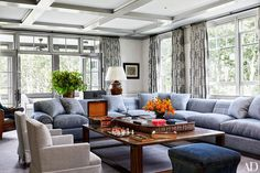 In the family room, a bespoke De Angelis sectional sofa in a Rose Tarlow Melrose House linen blend is grouped with antique English armchairs clad in a Jasper fabric and a cocktail table custom crafted from reclaimed oak