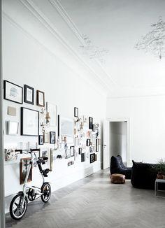 Gallery wall, mismatched art, picture frames, grey herringbone wood floor, high ornate ceiling, black sofa/armchair