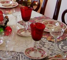 my Christmas table.  antique English dishes in red and pink, layered vintage lace linens & red crystal stemware.