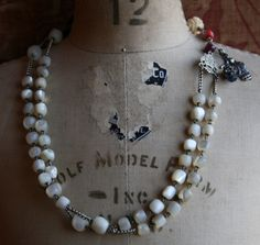 This gorgeous arrangement of vintage mother of pearl beads, a Joan of Arc medal, gemstones and south sea pearls creates a beautiful keepsake. Approx. 18 in length.