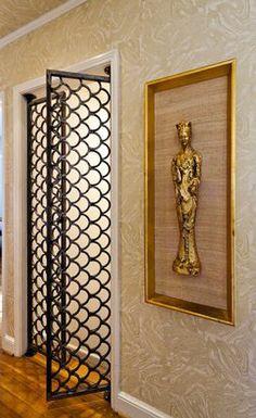 Custom-built iron gates in an art deco fish-scale motif replaced a solid door to lighten a once-dark hallway.    Terri Glanger Photography