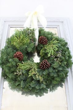 Simplest is usually best... wreath with cypress, evergreen, pinecones and simple white ribbon...