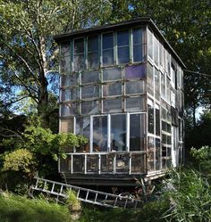 """Glass House Made from Recycled Windows in Copenhagen's Freetown Christiania Commune. Considered """"architecture without architects"""" there is a strong political will to tear the houses down. they are illegal, follow no building code, have no permits, yet they are safe for the next year as a local battle ensues."""