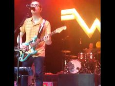 Weezer drummer, Patrick Wilson, catches a frisbee during a concert