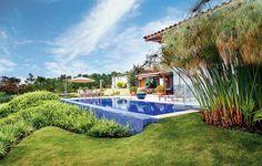 A piscina com fundo infinito é sonho de consumo de muita gente. No projeto da paisagista Paula Gabi, a caída do terreno foi disfarçada com as espécies bela-emília e íris-azul. Repare como o azul das pastilhas contrasta com o verde do jardim