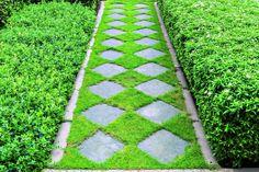 Ułożone w trawie betonowe płyty tworzą efektowny motyw szaro-zielonej szachownicy./Fot. WorldWide shutterstock