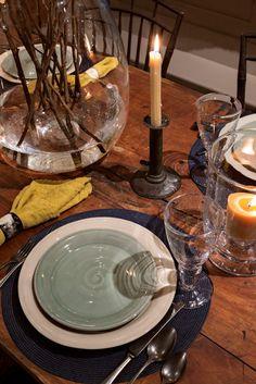 SIMON PEARCE INSTALLATION. A rustic sawbuck table contrasts Simon Pearce's elegant glassware, pottery, pewter, and linens.  Robert Benson Photography