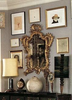 Antique mirror with mix of art on gray wall anchored by black bureau and lamp--Foyer of Kate Spade #antiques #thehighboystyle