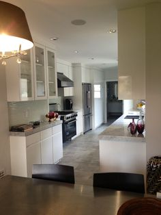 All white kitchen.  Carrera counter tops. White Lacquer cabinets.