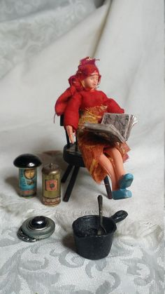 Here is a sweet little gypsy doll. Approximately 4 inch tall. Made of all rubber. She is poseable. Comes with all the little accessories. There is a unique black cast iron kettle & 1 spoon. I believe the spoon was made by theTootsie company back in the 1940s. 2 jars of potions, one spell book and a make-believe crystal ball. Her chair is for display only. You can find some Wizard and witch furniture in my shop under dollhouse miniatures.