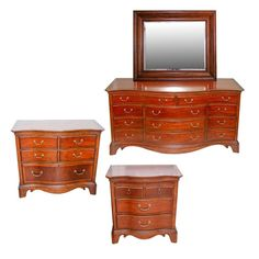A Thomasville bedroom, nightstand, dresser and chest. The set includes four wood pieces in a cherry finish of wood and veneer including a dresser with a serpentine front, a wood and veneer inlaid top with eleven drawers with dove tail construction, pewter style antique pulls and brass tone locks, a beveled and curved skirt with bracket style feet and a mirror that sits on the dresser that has a square wood frame with beveled edges and a mahogany finish with metal brackets for hanging. The…