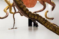 Suspendue à un plafond de 22 mètres de haut, Wu Zei est une sculpture massive de l'artiste chinoisHuang Yong Ping. Il dépeint une créature semblable àune