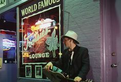 "Nashville -- Music City: A musician stands holding his guitar outside Tootsie's Orchid Lounge, a country music bar. Nashville is known as ""Music City."" Many country music legends have performed at the famous Grand Ole Opry. (Photo Credit: Catherine Karnow/CORBIS)"