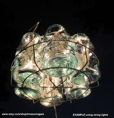String-Light Chandelier: Easy to 'stuff' a vintage glass light fixture with string lights and place in a wire basket. Use regular string lights indoors, or solar lights outdoors. Firefly Mason Jars, Mason Jar Solar Lights, Mason Jar Lighting, Jar Lights, Mason Jar Diy, Mason Jar Chandelier, Outdoor Chandelier, Hanging Chandelier, Outdoor Lighting