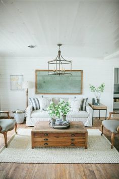 eclectic living room, French side chairs, flat (map)/file coffee table, distressed wood floors, lantern pendant lighting