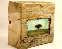 """The carved space in this reclaimed barn wood block makes home or a window for the iconic apple tree and a retreat for your thoughts. The illustration is covered with layers of pigmented beeswax (encaustic) and is finished off with rich brown stain. The block measures 6""""x 6"""" x 3"""" deep, can hang on the wall or rest on a shelf. The barn wood block is beautiful from any angle and the natural element gives it a wonderful presence."""