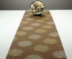 "Brown Table Runner - Table Runner Brown 60 inch long with gold metallic design by Proper Pillow. $44.00. This is beautiful golden/metallic design screen printed on dark brown, heavy-weight cotton.   Colors include gold, metallic white and natural. The florets are approximately 4 inch in diameter.   This table runner is 14"" wide and 60"" long but is also available in 72inch, 90inch, 108inch and 120inch length.   This table runner is Dry Clean Only."