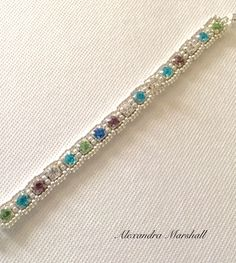 """This one of a kind Multicolored and Clear Crystal tennis bracelet by Alexandra Marshall seems to """"pick up"""" whatever color it is near. 7"""" long with magnetic clasp and sterling silver safety chain. #B2520."""
