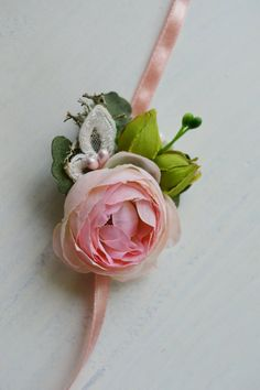 This lovely baby tieback features pink ranunculus, mint green leaves, lime green rose buds, delicate berries, natural grey moss and ivory embroidered