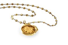 Fleur de Lis Seal Pendant necklace in 18k yellow gold with 5 cts. t.w. yellow sapphires, $4,000; Catherine Angiel
